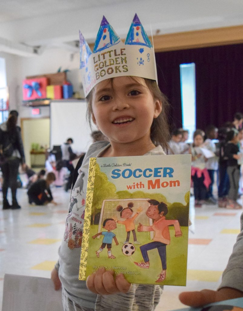 Little girl holds up 'Soccer with Mom' book.